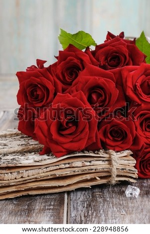 Bouquet of red roses on wooden table - stock photo