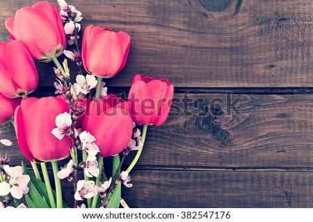 Bouquet of red tulips and branches of sakura on a wooden background with copy space for greeting message. Spring flowers. Spring background. Top view - stock photo