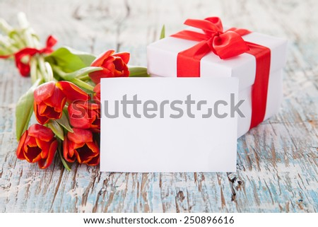 Bouquet of red tulips with gift and blank card on wooden planks.