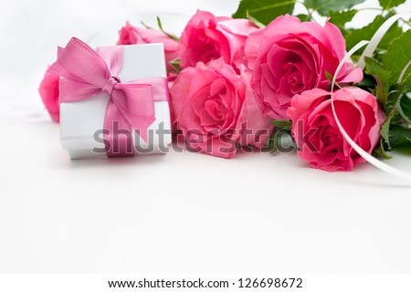 Bouquet of roses and gift box on white background - stock photo