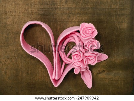 Bouquet of roses and heart silhouette on the wooden background - stock photo