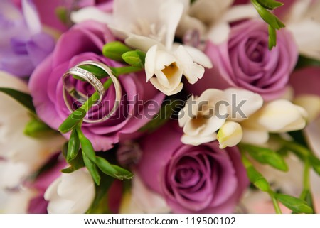 bouquet of roses and wedding rings - stock photo