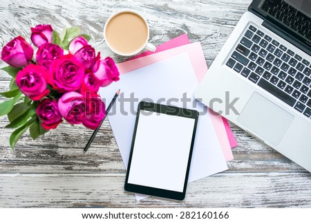 Bouquet of roses, cup of coffee, female hands with tablet and laptop on old wooden table. Top view - stock photo