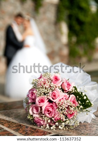 bouquet of roses lies on the background of the bridegroom and of the bride - stock photo
