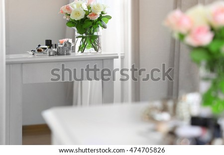 Bouquet of roses on light dressing table reflecting in mirror