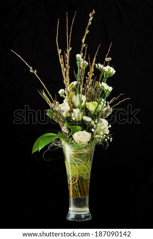Bouquet of roses, statice and pussy willows branches in glass vase on black background. - stock photo