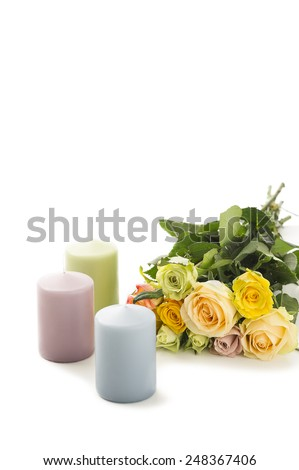 Bouquet of roses with a trio of pretty pastel candles to celebrate Valentines Day, Mothers Day or an anniversary arranged on a white background with copyspace for your greeting for a loved one - stock photo
