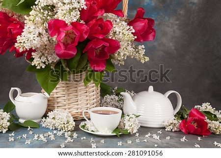 Bouquet of roses with lilac and tea cups for tea on the table - stock photo