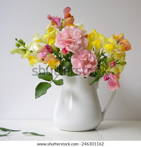 Bouquet of snapdragon flowers and roses in a vase. Floral decoration with antirrhinum majus and roses. - stock photo