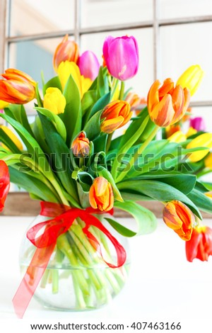 Bouquet of spring colorful tulip flowers in glass vase. Summertime indoors vertical closeup image - stock photo