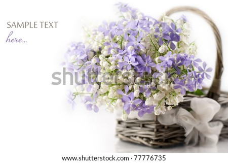 Bouquet of spring flowers in basket on white background - stock photo