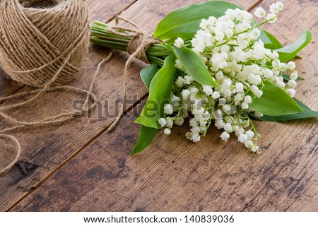 Bouquet of spring flowers lilys of the valley with a ball of brown twine - stock photo