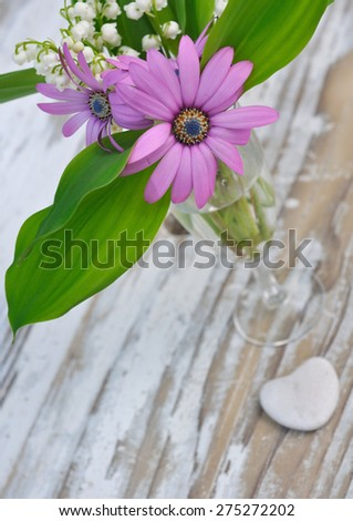 bouquet of spring flowers on a wooden planck with a little heart - stock photo
