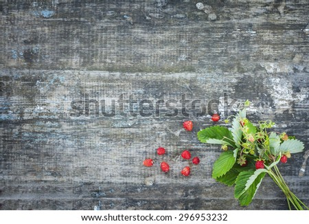 bouquet of strawberries on the board. Summer berries collected in the forest. Rural texture . Greeting Card fashion labels . - stock photo