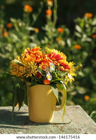 Bouquet of summer flowers in a yellow mug - stock photo