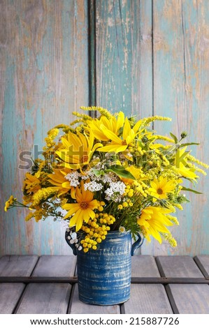 Bouquet of sunflowers and wild flowers on wooden table, copy space - stock photo