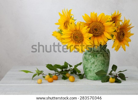 Bouquet of sunflowers in old ceramic jug against a white wooden wall. In the foreground branches with ripe cherry plum - stock photo