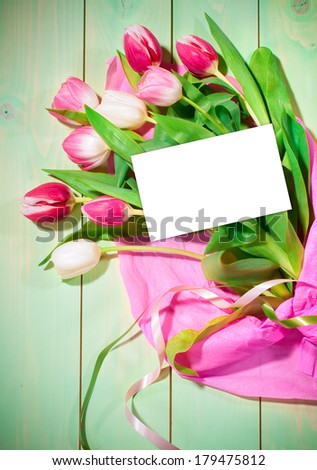 Bouquet of  tulips and card on green wooden background - stock photo