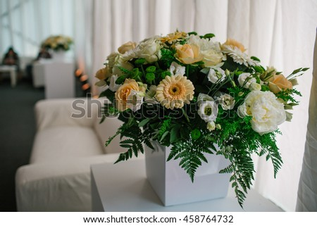 Bouquet of white flowers and greenery stand in the cube vase in a white room