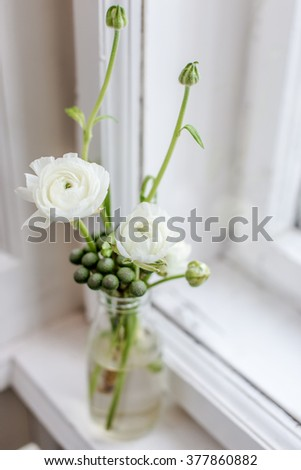 Bouquet of white ranunculus in glass vase near the window