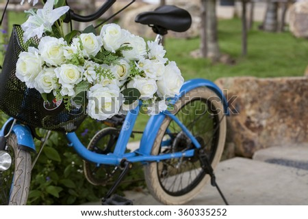 bouquet of white rose flowers on a bicycle basket