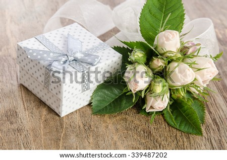 Bouquet of white roses and gift box on wooden background - stock photo