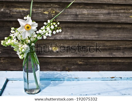Bouquet of white spring flowers in a bottle on blue wooden table on a background of old boards - stock photo