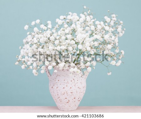 Bouquet of white tiny baby's-breath flowers in an antique ceramic vase - stock photo