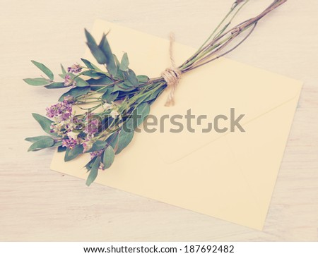 bouquet of wild flowers and an envelope on the table, instagram effect - stock photo