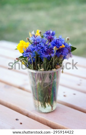 Bouquet of wildflowers in plastic glass on wooden table