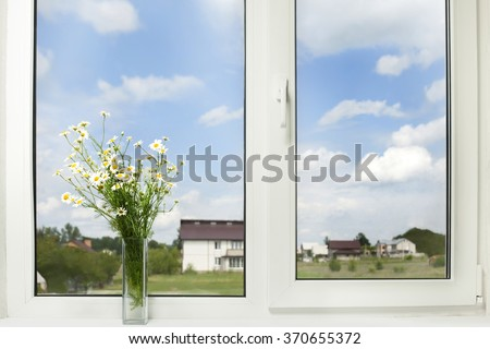 Bouquet of wildflowers on a plastic window - stock photo