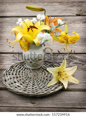 Bouquet of yellow and orange lilies in a vintage vessel of milk on wooden background - stock photo