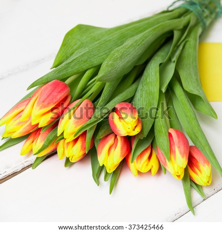 Bouquet of yellow red tulips on  white wooden background - stock photo