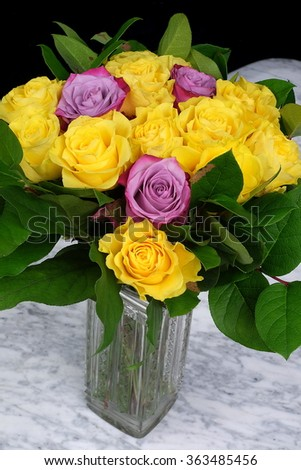 Bouquet of yellow roses with three purple in the glass vase on the marble table with a black background - stock photo