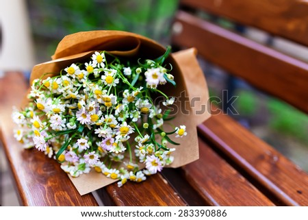 Bouquet on craft paper decoration with daisies in vintage wood background. - stock photo