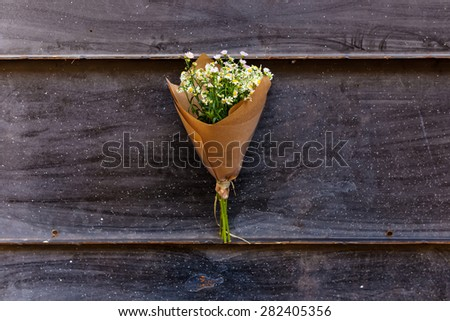 Bouquet on craft paper decoration with daisies over old black metal background. Close up on bouquet. - stock photo