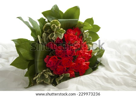 Bouquet with red roses on satin for background use - stock photo