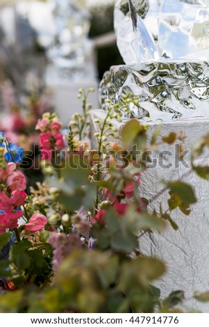 Bouquets of pink flowers surround an ice figure - stock photo