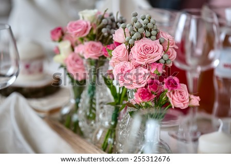 Bouquets of roses on a festive wedding table in the restaurant. - stock photo