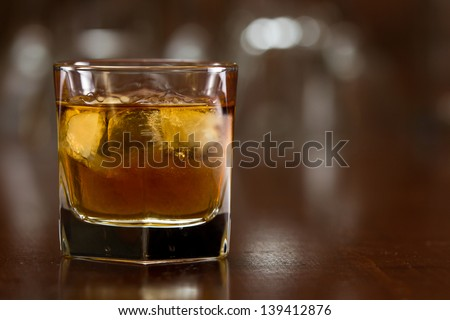 bourbon whiskey served with ice on a out of focus busy bar - stock photo