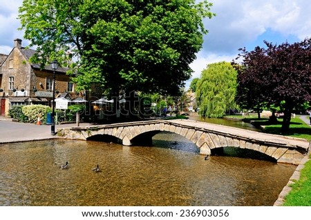 BOURTON-ON-THE-WATER, UK - JUNE 12, 2014 - Stone footbridge across the River Windrush with tea-rooms to the rear, Bourton on the Water, Gloucestershire, England, UK, Western Europe, June 12, 2014. - stock photo