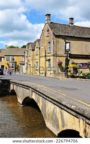 BOURTON ON THE WATER, UK - JUNE 12, 2014 - Stone footbridge across the River Windrush with the Kingsbridge Inn to the rear, Bourton on the Water, Gloucestershire, England, UK, Europe, June 12, 2014. - stock photo