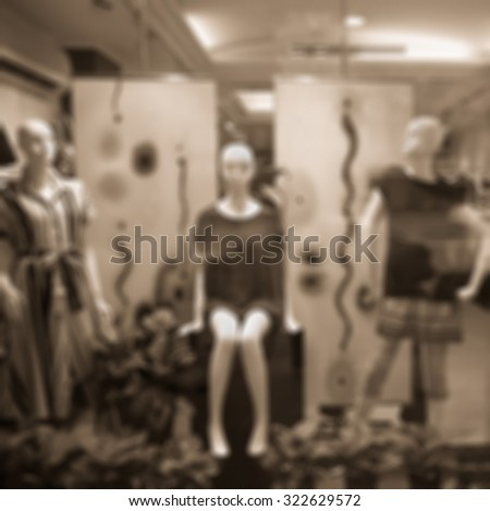 Boutique window with dressed mannequins. Boutique display window with mannequins in fashionable dresses. Sepia tone. - stock photo