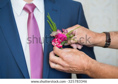 Boutonniere on hip trendy groom at wedding