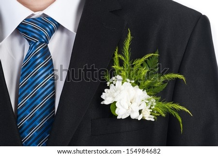 Boutonniere On Jacket. Wedding day moment and bridal concept.  Stylish bridal decoration on suit.  - stock photo