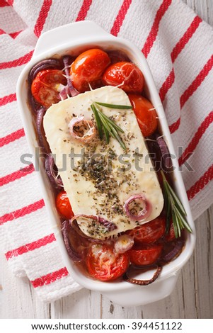 Bouyiourdi: Feta cheese baked with tomatoes and onions in baking dish closeup. Vertical view from above