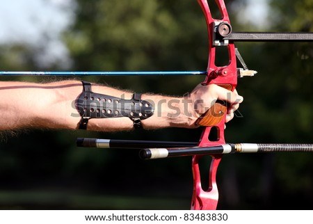 Bow hunter hands holding compound bow, closeup - stock photo