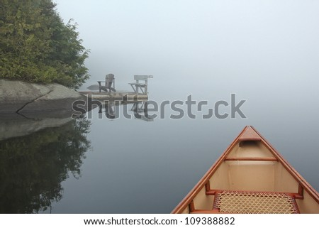 Bow of a Canoe on a Misty Lake in Northern Ontario with a Shoreline Dock and Chairs in the Background - stock photo
