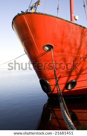 Bow of a red ship tied up at a quay