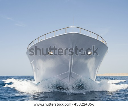 Bow of large luxury motor yacht sailing at sea on tropical ocean with wave